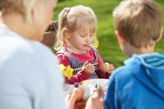 Mère et enfants décorant des oeufs de pâques Photo stock