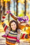 Mère et fille jouant en parc d'automne Photographie stock libre de droits