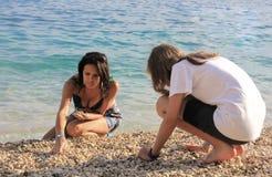 Mère et fille sur la plage en pierre Photographie stock libre de droits