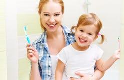 Mère heureuse de famille et enfant de fille balayant son toothb de dents Photos stock