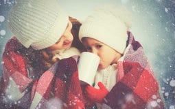 Mère heureuse et enfant de famille buvant du thé chaud sur l'OU de promenade d'hiver Images libres de droits