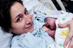 Mère heureuse retenant la chéri nouveau-née après naissance Photos libres de droits