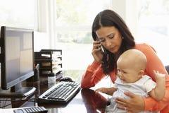 Mère hispanique avec le bébé travaillant dans le siège social Photos stock