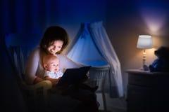 Mère lisant un livre au petit bébé Images libres de droits