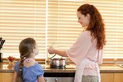 Mère montrant à sa fille ce qui cuisson de shes Images stock