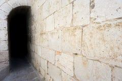 Mörk passage med den antika stenväggen Arkivbild