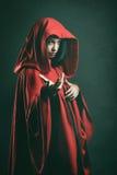 Mörk stående av en härlig kvinna med den röda kappan Royaltyfri Bild