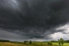 Mörka stormiga moln över havrefält på sommar Arkivfoton