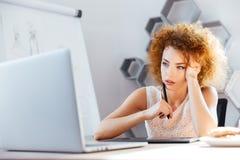 Märkes- användande bärbar dator för eftertänksam kvinna och grapic minnestavla på arbetsplats Arkivbilder