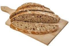Mörkt Multigrain bröd släntrar skivat på skärbrädan som isoleras på vit bakgrund Royaltyfri Foto