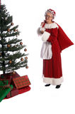Mrs. Claus. Mrs Santa Claus in a fur trimmed red velvet dress and bonnet with a bag of toys over her shoulder delivering christmas presents under the tree stock photography