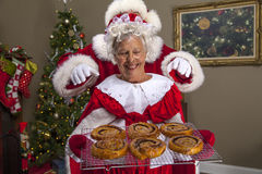 Mrs Claus bakes a treat for Santa. Color, horizontal image of Santa trying to sneak around the back of Mrs Claus to get cinnamon rolls royalty free stock image