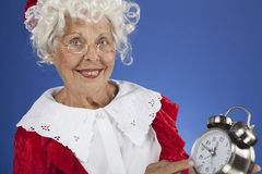 Mrs Claus with a clock at midnight. Horizontal, color, close up of Mrs Claus holding an alarm clock that says it is almost midnight royalty free stock photo
