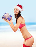 Mrs claus with gift on beach. Beautiful mrs claus with gift wearing in bikini costume on beach royalty free stock images