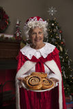 Mrs Claus holding fresh baked cinnamon rolls. Vertical, color image of Mrs Claus holding a plate of fresh baked cinnamon rolls while standing in front of the stock photo