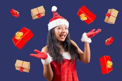 Mrs. Claus juggle with Christmas gifts. Cheerful Mrs. Claus looks at the camera and juggle with Christmas gifts. Xmas boxes are falling around Mrs. Santa Claus stock photos