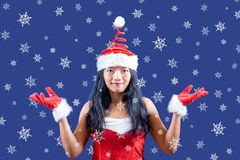 Large snowflakes fall around Mrs Claus. Mrs. Claus looks to the camera with her hands shows snowflakes. Large snowflakes fall around Mrs Claus royalty free stock photos