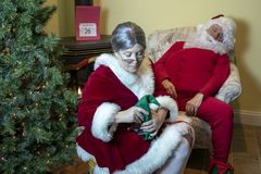 Mrs. Claus massaging Santa`s tired feet royalty free stock photos