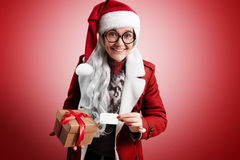 Mrs claus series. Mrs Claus happily smiling with gray hairs, weraing Santa hat, traditional sweater, round glasses and red warm coat holds beautiful craft box royalty free stock photography