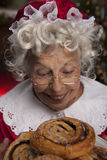 Mrs Claus Smelling fresh baked cinnamon rolls. Vertical, color image of Mrs Claus smelling the fresh baked cinnamon rolls stock photos