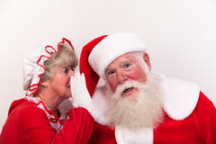 Mrs Claus tells secret. Mrs Claus whispers a secret into Santas ear. Perhaps she knows who has been naughty or nice royalty free stock image
