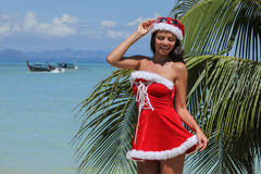 Mrs. Claus on tropical beach Stock Image