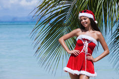 Mrs. Claus on tropical beach. Beautiful woman in Mrs. Claus custume on tropical beach with palms, Christmas vacations concept royalty free stock photos