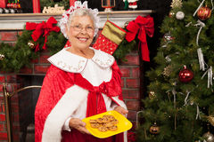 Mrs. Clause holding a plate of cookies. In front of the fireplace and beside the Christmas Tree stock photos