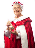 Mrs. Clause with Christmas ornament. Mrs. Clause, isolated on white, holding a gold Christmas ornament stock images