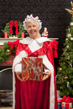 Mrs. Clause holding a Christmas present. Mrs. Clause standing in front of the fireplace and beside the Christmas Tree holding a present stock images