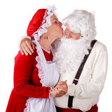Mrs. Kissing Santa Claus. Mrs. Santa stretching to kiss Santa Claus. Isolated on white stock photography