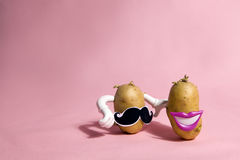 Mrs and mister patato. A pop and minimal potato portrait on a pink background Royalty Free Stock Photo