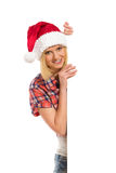 Mrs. Santa biting a lip. Blond woman in red santa's hat standing behind a big banner and biting a lip. Waist up studio shot isolated on white Royalty Free Stock Photography