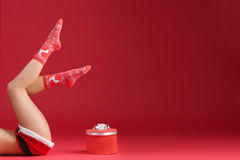 Mrs santa claus legs in Christmas stockings. With christmas gift on red background Stock Photo