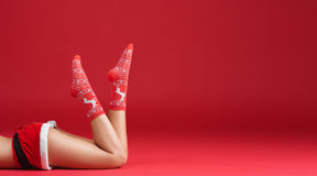Mrs santa claus legs in Christmas stockings. On red background Stock Photography