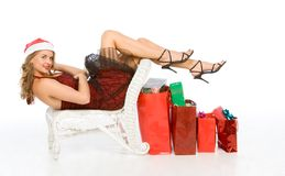 Mrs Santa Claus with lot of Christmas presents. Blonde woman in Santa hat lying down with her legs and high heel shoes over row of colorful red shopping bags stock images