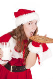 Mrs Santa eating big cookie Stock Photography