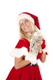 Mrs santa money hide. Mrs. Santa Clause holding a hand full of one hundred dollars in her hands with a smile on her face Royalty Free Stock Photography