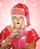Mrs. Santa opening a gift box Stock Image