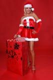 Mrs. Santa's Christmas Bag. Sexy Mrs Santa with a large bag full of christmas gifts Royalty Free Stock Photography