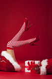 Mrs Santa's legs. Mrs santa claus legs in striped stockings with christmas gifts stock images