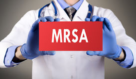 MRSA methicillin-resistant Staphylococcus aureus. Doctor`s hands in blue gloves shows the word MRSA methicillin-resistant Staphylococcus aureus. Medical concept stock photo