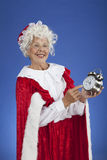 Ms Claus pointing at the clock. Vertical, color image of Mrs Claus holding an alarm clock pointing at the time so Santa won't be late royalty free stock photo