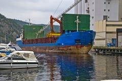 Ms vestvind. Is docked at the port of halden and fill grain from halden grain silo, vessel's details, ship type: cargo, year built: 1985, length x breadth: 81 Stock Photos
