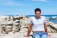 Más viejo hombre sonriente que se sienta en la playa Imagen de archivo libre de regalías