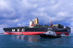 MSC mega container ship pulled by a tugboat Stock Photography