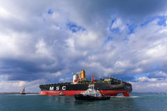 MSC mega container ship pulled by a tugboat Stock Image