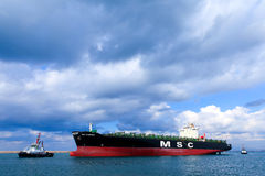 MSC mega container ship pulled by a tugboat Stock Images