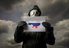 A máscara de gás e Ucrânia traçam com bandeira do russo Fotos de Stock Royalty Free