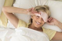 Máscara del sueño de la mujer que lleva feliz en cama Imágenes de archivo libres de regalías